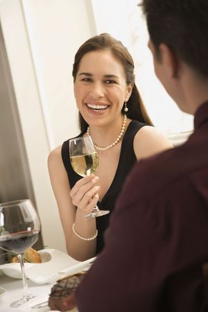 half length posed: Mid adult Caucasian couple smiling and drinking wine and dining. Stock Photo
