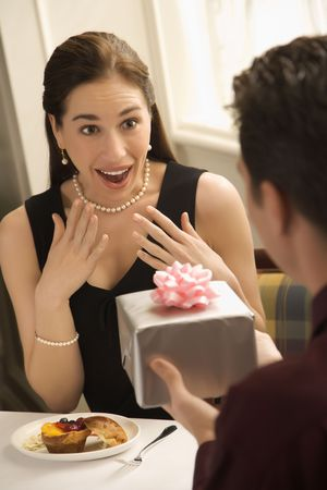gasp: Mid adult Caucasian man presenting wrapped gift to surprised woman at restaurant. Stock Photo