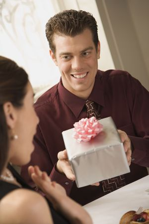 Mid adult Caucasian man presenting wrapped gift to surprised woman at restaurant. Stock Photo - 2190512