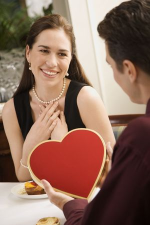Mid adult Caucasian man giving a heart shaped box of chocolates to woman at restaurant. photo
