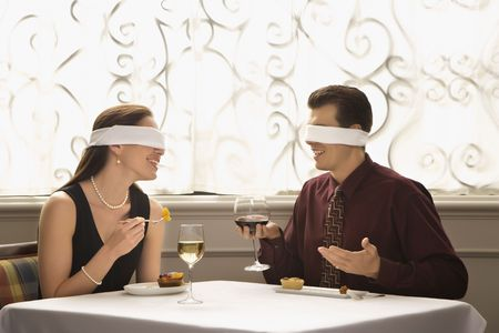 Mid adult Caucasian couple dining in a restaurant with blindfolds over eyes. photo