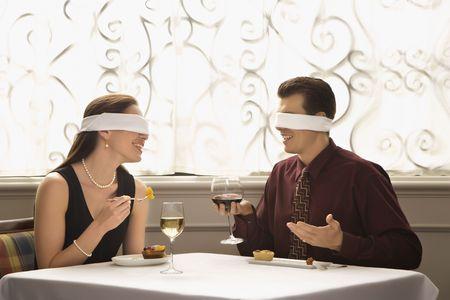 ojos vendados: Pares caucásicos del adulto mediados de que cenan en un restaurante con los blindfolds sobre ojos.