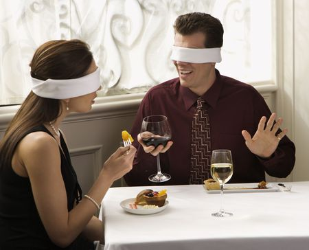 image date: Mid adult Caucasian couple dining in a restaurant with blindfolds over eyes. Stock Photo