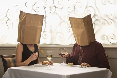 image date: Mid adult Caucasian couple dining in a restaurant with paper bags over heads.