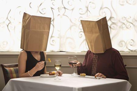 Pares caucásicos del adulto mediados de que cenan en un restaurante con las bolsas de papel sobre las cabezas. Foto de archivo