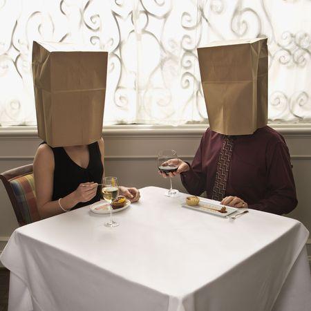Tussentijdse volwassen blanke paar dineren in een restaurant met een papieren zak over het hoofd.