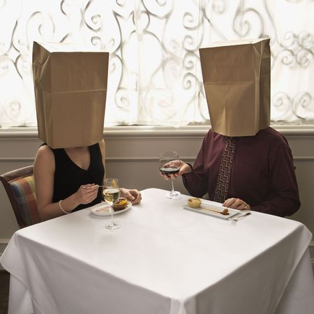 anonymous: Mid adult Caucasian couple dining in a restaurant with paper bags over heads.