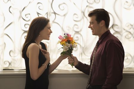 half length posed: Mid adult Caucasian man presenting surprised woman with bouquet of flowers.