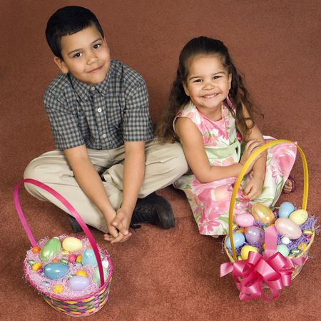 Hispanic brother and sister sitting on floor with Easter baskets looking up at viewer smiling. photo