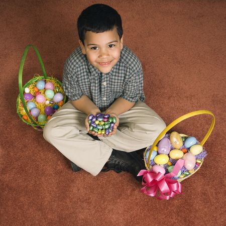 Hispanic boy sitting on floor with two Easter baskets holding chocolate candy eggs in his hands looking up at viewer smiling. photo