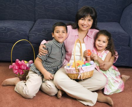Family sitting on floor with Easter baskets smiling and looking at viewer. photo