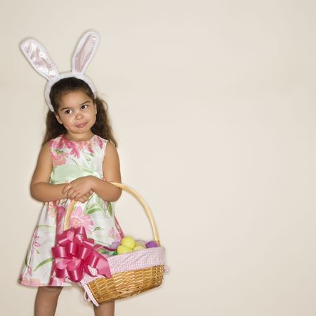 Hispanic girl wearing bunny ears holding Easter basket.