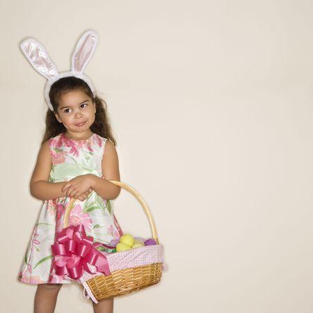 bunny ears: O�dos del conejito de la muchacha que usan hisp�nica que sostienen la cesta de Pascua.