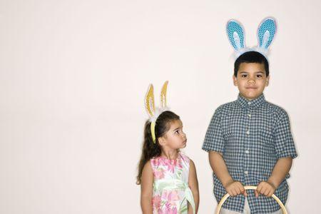 bunny ears: Hispanic chica busca chico hispanos a la celebraci�n de la Pascua cesta ambos llevaban bunny las orejas.  Foto de archivo