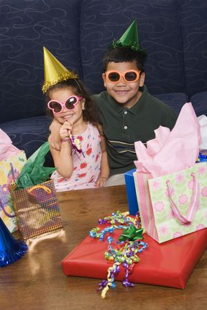 customs and celebrations: Hispanic brother and sister wearing sunglasses and party hats sitting with presents having a birthday party. Stock Photo