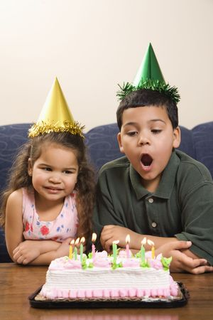 customs and celebrations: Hispanic girl and boy wearing party hats preparing to blow candles out on birthday cake.