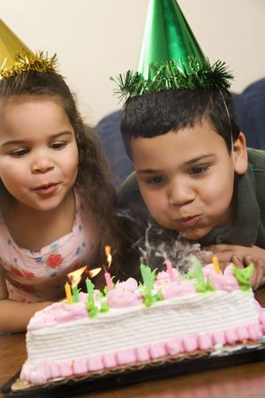 customs and celebrations: Hispanic girl and boy wearing party hats blowing out candles on birthday cake.