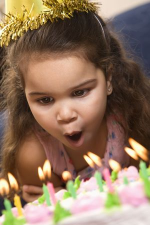 Hispanic girl wearing party hat blowing out candles on birthday cake.