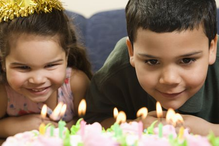 customs and celebrations: Hispanic girl and boy leaning in close looking at lit candles on birthday cake and smiling.