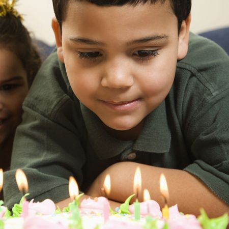 Hispanic boy looking down wishfully at lit candles of birthday cake with girl peeking in over his shoulder. photo