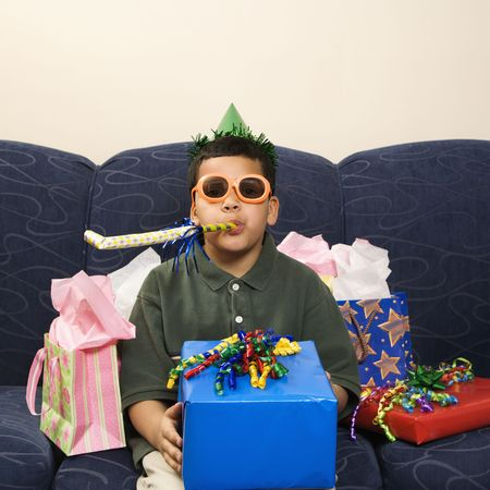 party favors: Hispanic boy with birthday party favors and presents looking at viewer.