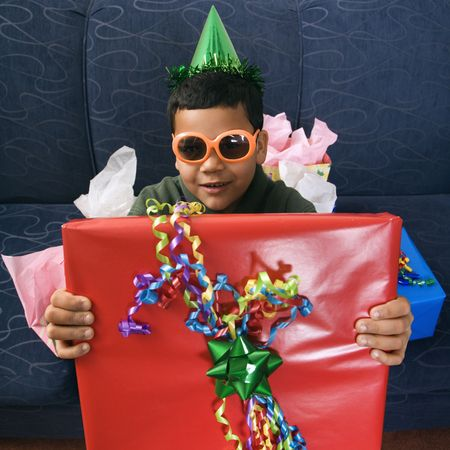customs and celebrations: Hispanic boy wearing party hat and sunglasses holding large birthday present smiling and looking at viewer. Stock Photo