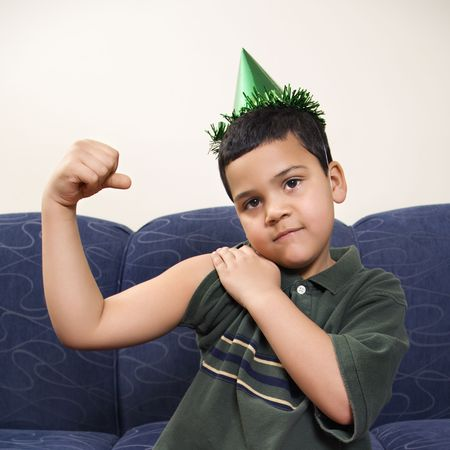 goofing: Hispanic boy wearing party hat playfully flexing arm muscle while looking at viewer.