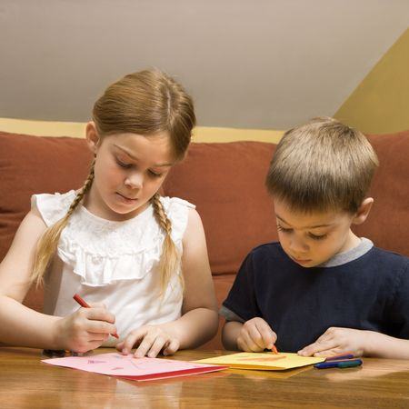 Caucasian boy and girl drawing on paper with crayons. Stock Photo - 2190280