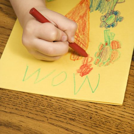 Caucasian boy drawing on yellow paper with crayons. Stock Photo - 2190248