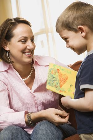 Caucasian boy giving mid adult mother a drawing. photo