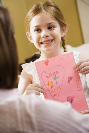 Caucasian girl giving mid adult mother a drawing. Stock Photo - 2190619