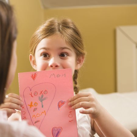 Caucasian girl giving mid adult mother a drawing. Stock Photo - 2204645