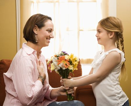 Caucasian girl giving mid adult mother a drawing. Stock Photo - 2190291