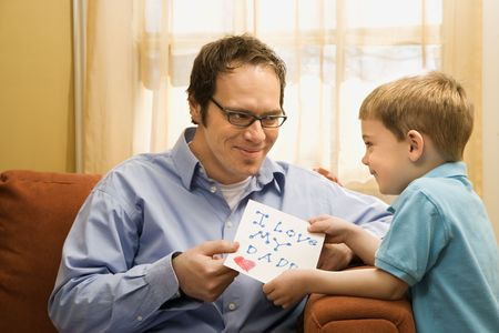 Caucasian boy giving mid adult father a drawing. photo
