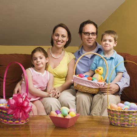 Caucasian family on couch holding Easter basket and looking at viewer. photo