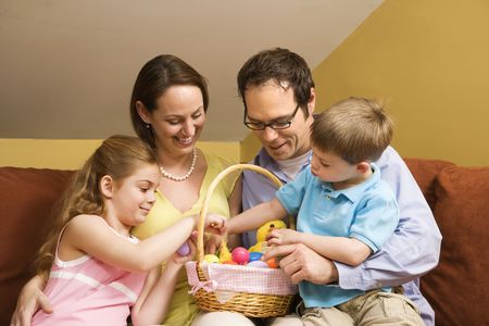 Caucasian family on couch looking at Easter basket.  photo
