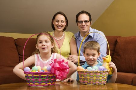 Caucasian family with Easter baskets looking at viewer.  photo