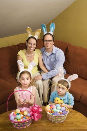 Caucasian family wearing rabbit ears with Easter baskets looking at viewer.  photo