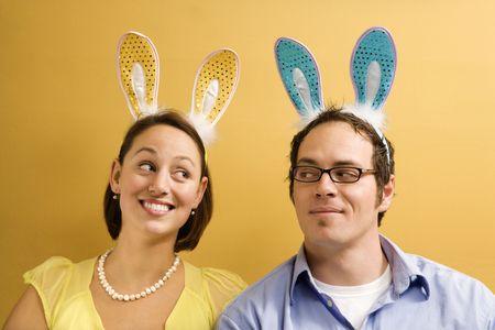 mid adult couple: Mediados de adultos de raza cauc�sica par llevar orejas de conejo y buscando el uno al otro.  Foto de archivo