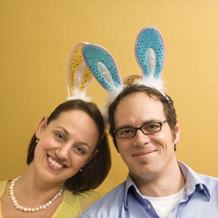 mid adult couple: O�dos del conejo de los pares mediados de cauc�sicos del adulto que usan y mirar el espectador. Foto de archivo