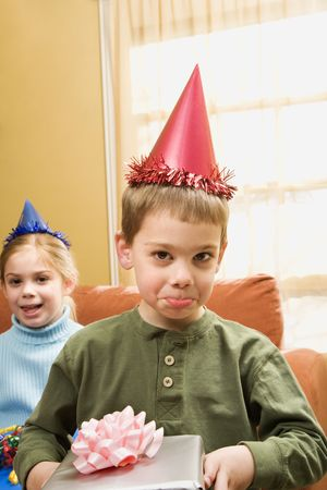 Caucasian boy wearing party hat pouting and looking at viewer. photo