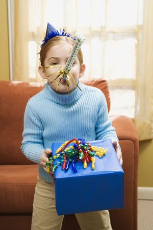 Caucasian girl blowing noisemaker and holding gift. photo