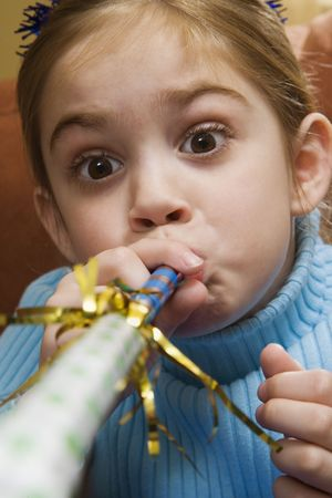 noisemaker: Caucasian girl blowing noisemaker and making facial expression.