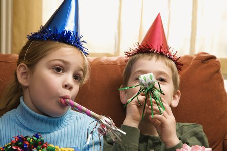 Caucasian children looking bored wearing party hats and blowing noisemakers. photo