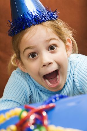 party hat: Caucasian girl wearing party hat holding gift  and looking at viewer with excited expression.