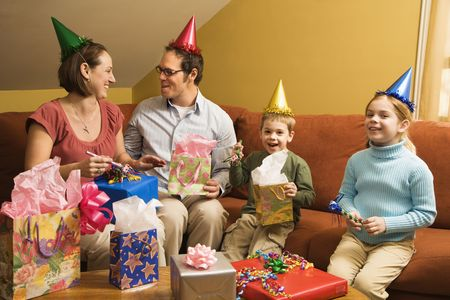 Caucasian family wearing party hats and celebrating a birthday party. photo