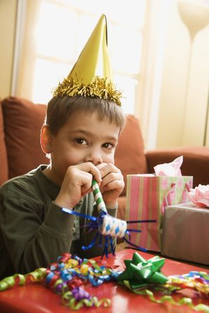 noisemaker: Caucasian boy at  birthday party looking at viewer blowing noisemaker.