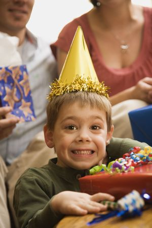 one person with others: Caucasian boy at  birthday party looking at viewer making facial expression.