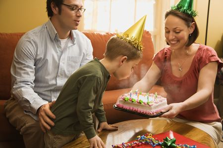 blowing out: Caucasian boy in party hat blowing out candles on birthday cake with family watching. Stock Photo