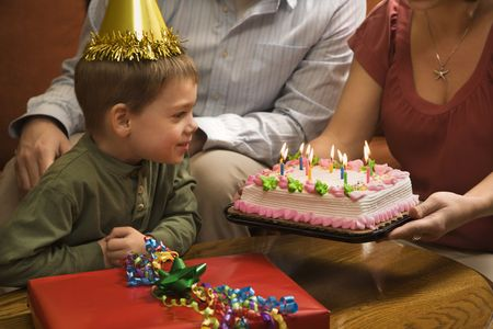 Caucasian boy in party hat with Birthday cake and . photo